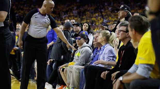 In this photo taken Wednesday, June 5, 2019, referee Marc Davis, left, gestures toward Golden State Warriors investor Mark Stevens, partially obscured in blue shirt, during the second half of Game 3 of basketball's NBA Finals (AP Photo/Ben Margot)