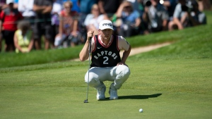 Canadian Mackenzie Hughes lines up a putt on the 13th green wearing a Toronto Raptors jersey during the first round of the Canadian Open golf championship in Hamilton, Ont., Thursday, June 6, 2019. THE CANADIAN PRESS/Adrian Wyld