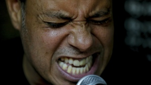 In this May 29, 2019 photo, Horacio Blanco, lead singer and guitarist of the Venezuelan ska band Desorden Publico, grimaces during a practice session at their studio in Caracas, Venezuela. (Fernando Llano / AP)