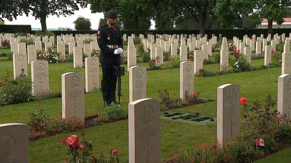 A Canadian soldier watches over a grave at Bretteville-sur-Laize Canadian War Cemetery in France.