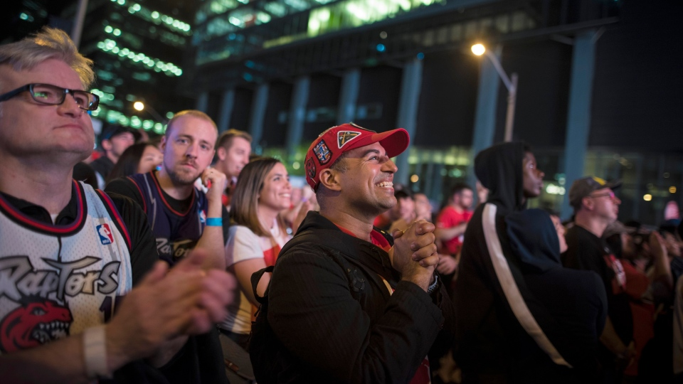 "Toronto Raptors fans react during Game 4 of the NBA Final between Toronto Raptors and Golden State Warriors in the ""Jurassic Park'' fanzone outside of Scotiabank Arena in Toronto on Friday June 7, 2019. THE CANADIAN PRESS/ Tijana Martin"