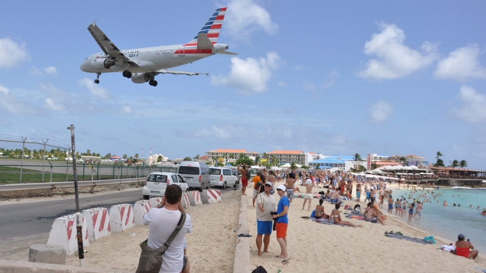 FILE -- A plane lands at the Princess Juliana International Airport as beachgoers watch in Philipsburg, St. Maarten, a Dutch Caribbean territory, Thursday, July 13, 2017. (AP Photo/Judy Fitzpatrick)