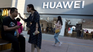 In this May 20, 2019, photo, a woman adjusts the glasses of a man outside a Huawei store in Beijing. (AP Photo/Ng Han Guan)