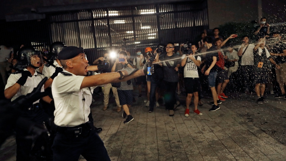 Police officers use pepper spray against protesters in a rally against the proposed amendments to the extradition law at the Legislative Council in Hong Kong during the early hours of Monday, June 10, 2019. (AP Photo/Vincent Yu)