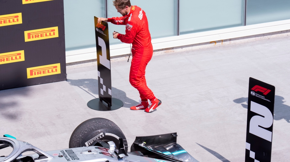 Ferrari driver Sebastian Vettel of Germany switches the standing markers to place Mercedes driver Lewis Hamilton of Great Britain second and Vettel first at the Canadian Grand Prix Sunday, June 9, 2019 in Montreal. THE CANADIAN PRESS/Paul Chiasson