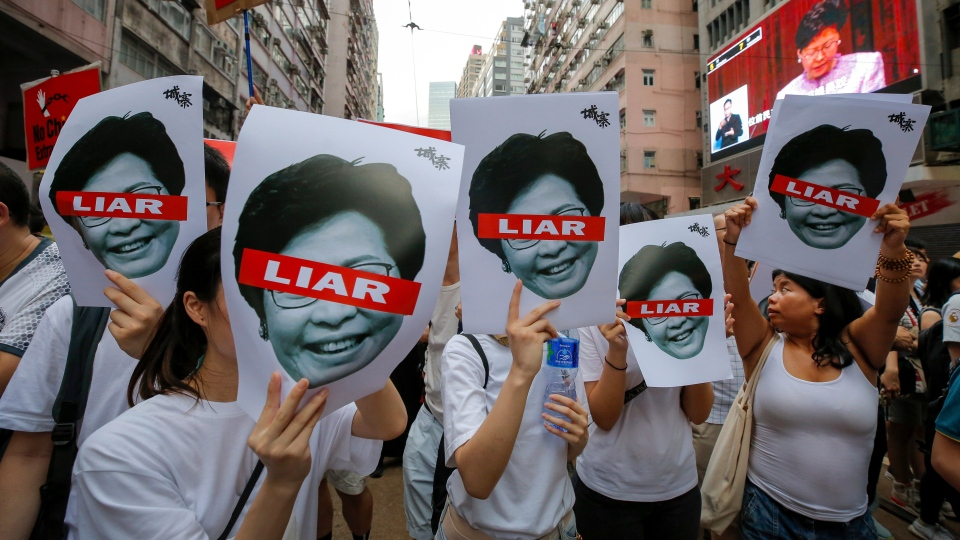 Protesters hold pictures of Hong Kong Chief Executive Carrie Lam as protesters march along a downtown street against the proposed amendments to an extradition law in Hong Kong Sunday, June 9, 2019. (AP Photo/Kin Cheung)