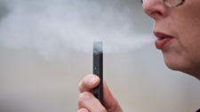 A woman exhales a puff of vapor from a Juul pen in Vancouver, Wash., Tuesday, April 16, 2019. (AP Photo/Craig Mitchelldyer)