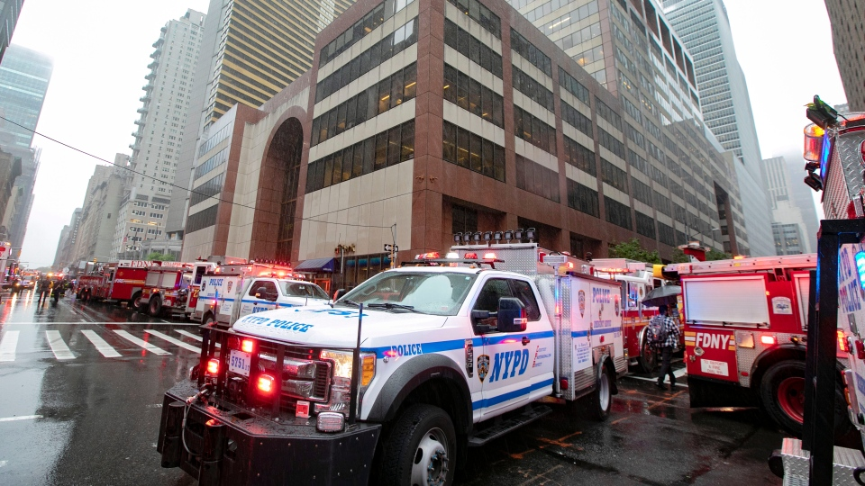 New York City Police and Fire Department vehicles surround the scene in front of a building in midtown Manhattan where a helicopter crash landed, Monday, June 10, 2019. (AP Photo/Richard Drew)
