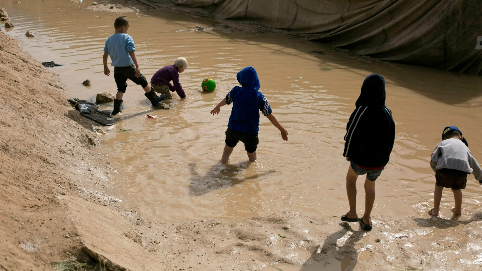 In this March 31, 2019 file photo, children play in a mud puddle in the section for foreign families at Al-Hol camp in Hasakeh province, Syria.  (AP Photo/Maya Alleruzzo, File)