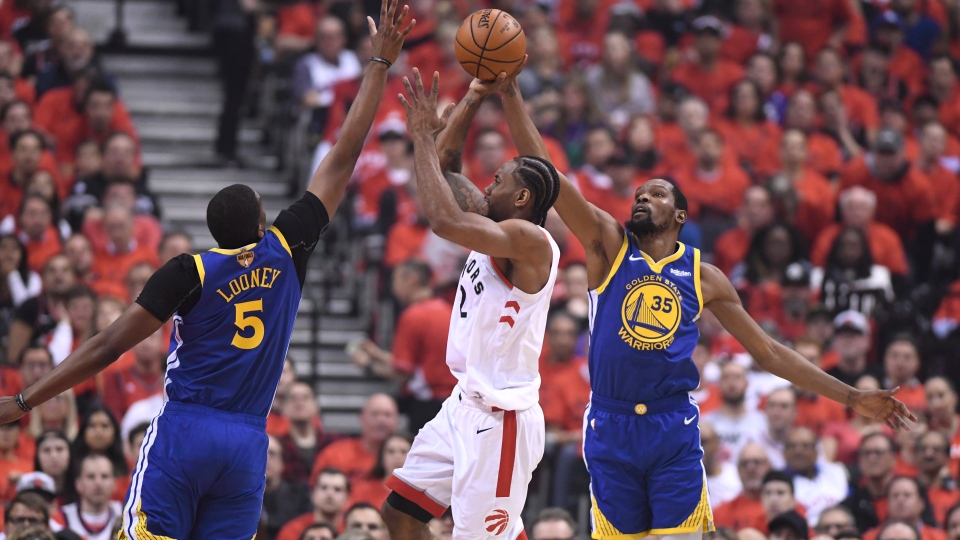 Toronto Raptors forward Kawhi Leonard (2) shoots while under pressure from Golden State Warriors centre Kevon Looney (5) and Kevin Durant during first half basketball action in Game 5 of the NBA Finals in Toronto on Monday, June 10, 2019. THE CANADIAN PRESS/Frank Gunn