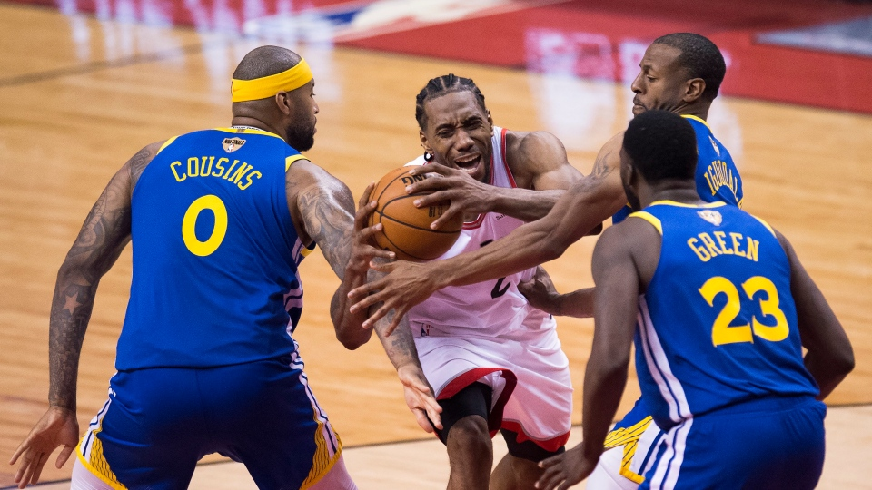 Toronto Raptors forward Kawhi Leonard (2) draws a foul as he drives to the net against Golden State Warriors centre DeMarcus Cousins (0), forward Draymond Green (23) and forward Andre Iguodala (9) during second half basketball action in Game 5 of the NBA Finals in Toronto on Monday, June 10, 2019. THE CANADIAN PRESS/Chris Young