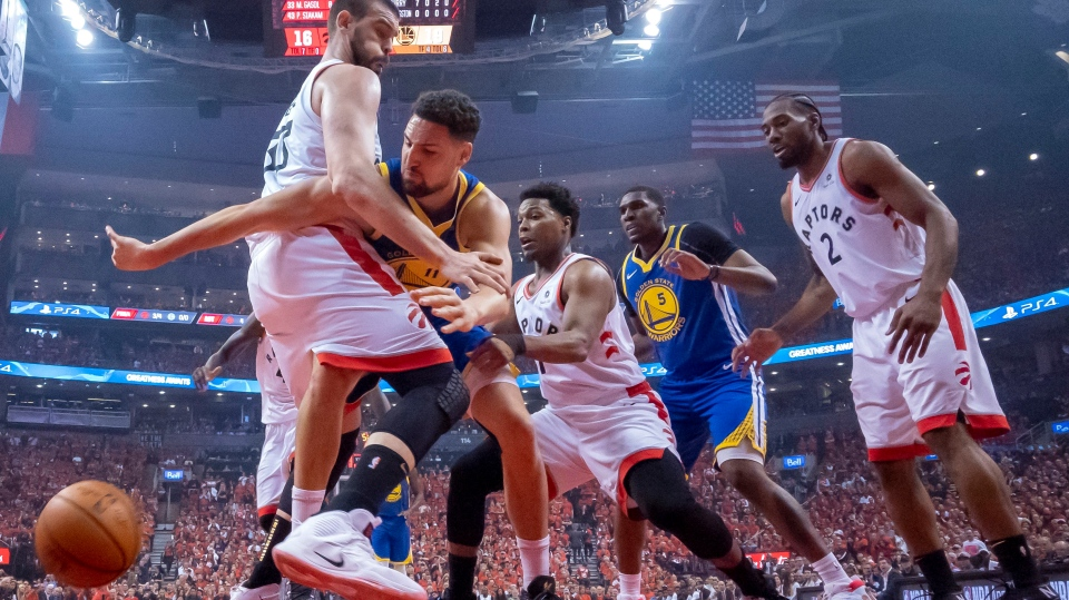 Golden State Warriors guard Klay Thompson (11) reaches for the ball past Toronto Raptors Marc Gasol as Raptors Kyle Lowry, Kawhi Leonard and Warriors Kevon Looney (5) look on during Game 5 of the NBA Finals in Toronto on Monday, June 10, 2019. THE CANADIAN PRESS/Frank Gunn