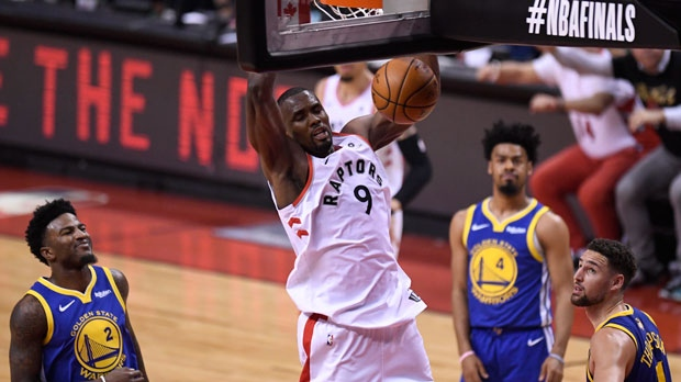 Toronto Raptors centre Serge Ibaka (9) throws down a dunk as Golden State Warriors forward Jordan Bell (2), Quinn Cook (4) and Klay Thompson look on during second half basketball action in Game 5 of the NBA Finals in Toronto on Monday, June 10, 2019. (THE CANADIAN PRESS/Frank Gunn)