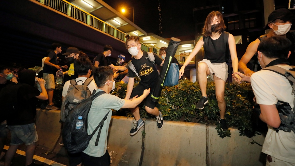 Protesters climb over a barrier as they rally against the proposed amendments to the extradition law at the Legislative Council in Hong Kong during the early hours of Monday, June 10, 2019. (AP Photo/Kin Cheung)