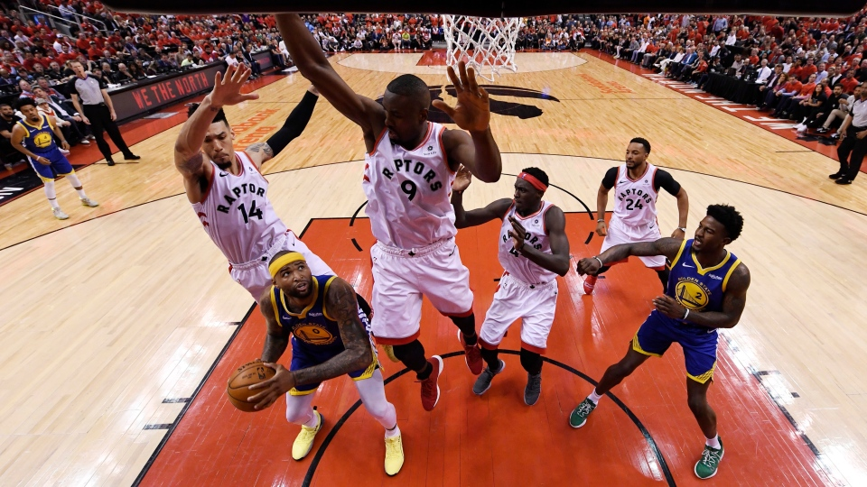 Golden State Warriors centre DeMarcus Cousins (0) looks to shoot as Toronto Raptors guard Danny Green (14) and centre Serge Ibaka (9) defend as forward Pascal Siakam (43), forward Norman Powell (24) and Warriors forward Jordan Bell (2) look on during second half basketball action in Game 5 of the NBA Finals in Toronto on Monday, June 10, 2019. (THE CANADIAN PRESS/Kyle Terada)