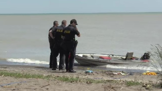 Police look on after a boat that capsized is pulled to shore on Lake Erie near Port Glasgow, Ont. on Tuesday, June 11, 2019. (Jim Knight / CTV London)