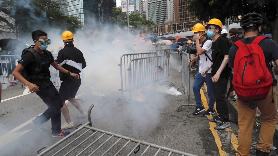Protestors react to tear gas during a large protest near the Legislative Council in Hong Kong, Wednesday, June 12, 2019. (AP Photo/Kin Cheung)