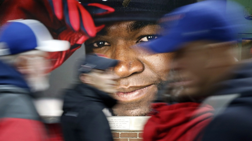 Fans walk past a photograph of Boston Red Sox's David Ortiz before a baseball game at Fenway Park, on Oct. 1, 2016. (Michael Dwyer / AP)