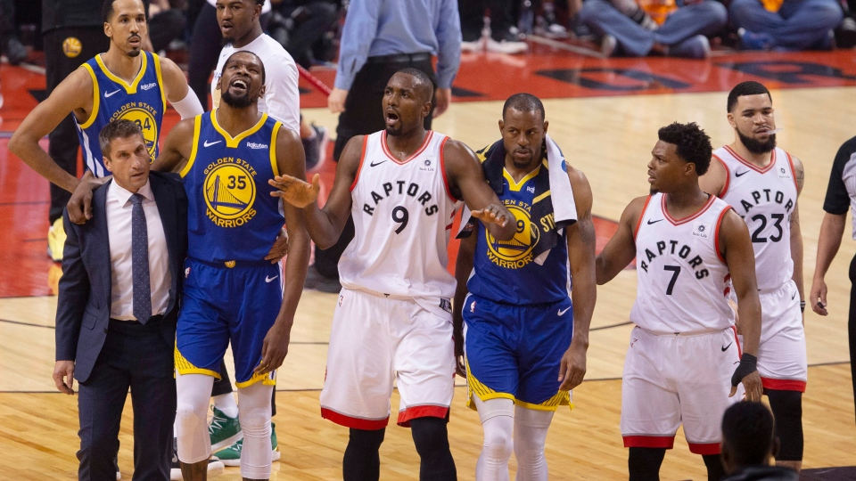 Golden State Warriors forward Kevin Durant (35) walks off the court after sustaining an injury as he's consoled by Toronto Raptors centre Serge Ibaka (9) as Warriors forward Andre Iguodala (9) and Raptors guard Kyle Lowry (7) look on during first half basketball action in Game 5 of the NBA Finals in Toronto on Monday, June 10, 2019. (THE CANADIAN PRESS/Chris Young)