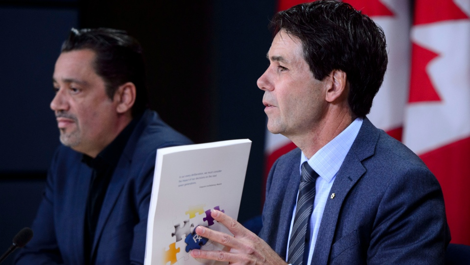 Dr. Eric Hoskins, Chair of the Advisory Council on the Implementation of National Pharmacare, is accompanied by Vincent Dumez, Member of the Advisory Council on the Implementation of National Pharmacare, during a press conference at the National Press Theatre in Ottawa on Wednesday, June 12, 2019. THE CANADIAN PRESS/Sean Kilpatrick