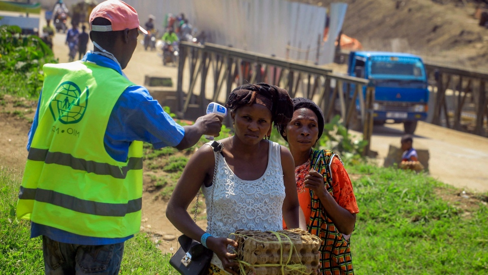 People crossing the border have their temperature taken to check for symptoms of Ebola, at the border crossing near Kasindi, eastern Congo Wednesday, June 12, 2019, just across from the Ugandan town of Bwera. (AP Photo/Al-hadji Kudra Maliro)