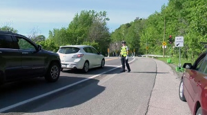 A police cadet directs traffic on Camillien Houde Way after new lights were installed (June 12, 2019)