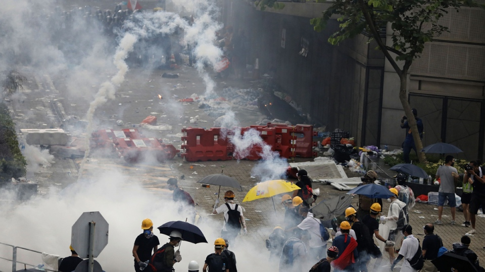 In this June 12, 2019, file photo, riot police fire tear gas toward protesters outside the Legislative Council in Hong Kong. (Vincent Yu / AP)