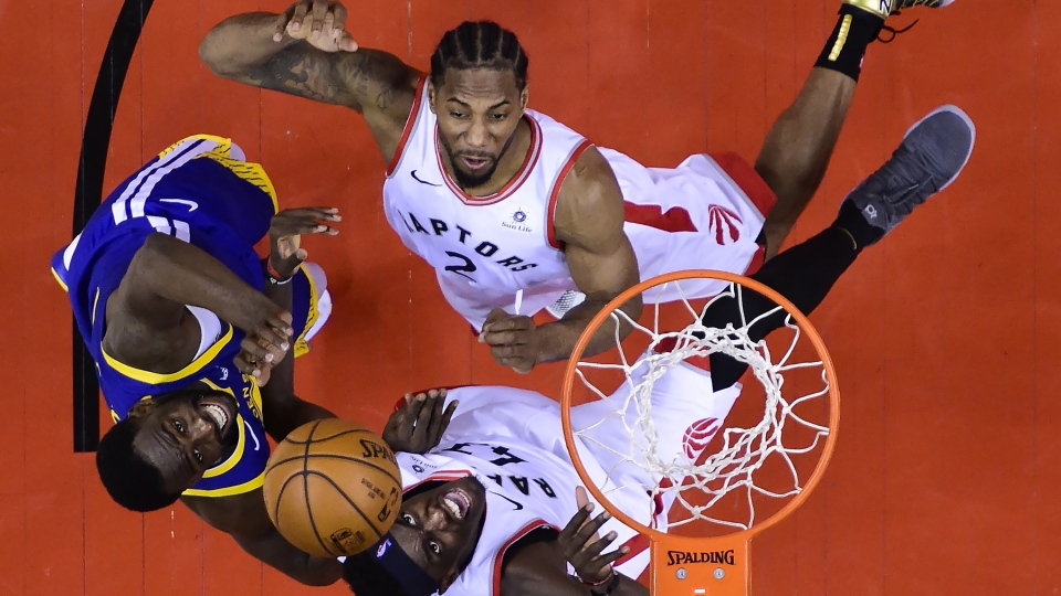 Toronto Raptors forward Pascal Siakam (43) and Toronto Raptors forward Kawhi Leonard (2) eye the ball against Golden State Warriors forward Draymond Green (23) during second half of Game 2 NBA Finals basketball action in Toronto on June 2, 2019. Even if Kawhi Leonard decides to leave Toronto as a free agent this summer, his impact on the Raptors figures to be felt for years to come. NBA most improved player candidate Pascal Siakam says Leonard has given him some valuable lessons during the Raptors' run to the NBA Finals. (THE CANADIAN PRESS/Nathan Denette)