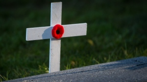 A cross bearing a poppy is seen by a military grave during a burial for Canadian and British Second World War airmen in Victoria, B.C., on Monday November 10, 2014. (Darryl Dyck / THE CANADIAN PRESS)