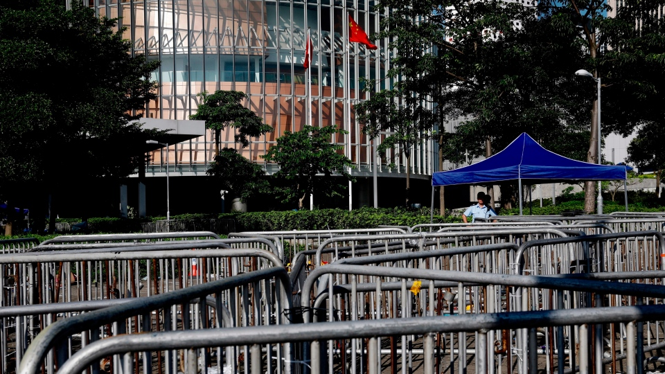A police officer looks out from barriers set up around the Legislative Council in Hong Kong on Friday, June 14, 2019. (AP Photo/Vincent Yu)