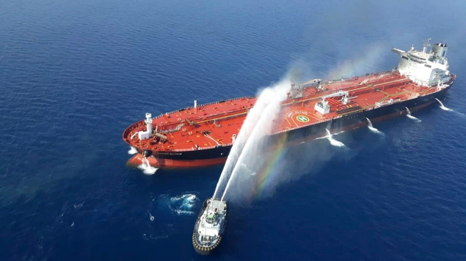 An Iranian navy boat sprays water to extinguish a fire on an oil tanker in the sea of Oman, Thursday, June 13, 2019. (AP Photo/Tasnim News Agency)