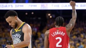 Toronto Raptors' Kawhi Leonard raises his fist following a basket as Golden State Warriors' Steph Curry walks away during second half NBA Finals Game 6 action in Oakland, Calif., Thursday, June 13, 2019. THE CANADIAN PRESS/Frank Gunn