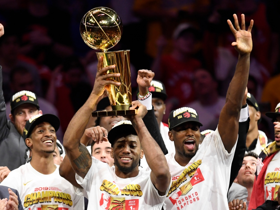Toronto Raptors forward Kawhi Leonard, centre, holds Larry O'Brien NBA Championship Trophy after defeating the Golden State Warriors basketball action in Game 6 of the NBA Finals in Oakland, Calif. on Thursday, June 13, 2019. Raptors have won their first NBA title in franchise history. THE CANADIAN PRESS/Frank Gunn