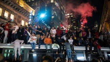 Toronto Raptors fans celebrate atop a transit vehicle following the Raptors' defeat of the Golden State Warriors in game 6 of the NBA Finals to win the NBA Championship, in Toronto, Friday, June 14, 2019. (THE CANADIAN PRESS/Tijana Martin)