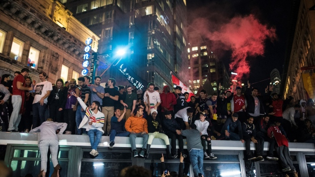 Toronto Raptors fans celebrate atop a transit vehicle following the Raptors' defeat of the Golden State Warriors in game 6 of the NBA Finals to win the NBA Championship, in Toronto, Friday, June 14, 2019. THE CANADIAN PRESS/Tijana Martin