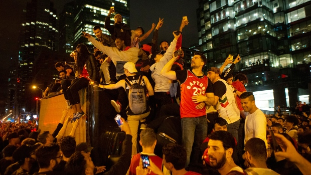 Toronto Raptors fans celebrate atop a vehicle following the Raptors' defeat of the Golden State Warriors in game 6 of the NBA Finals to win the NBA Championship, in Toronto, Friday, June 14, 2019. THE CANADIAN PRESS/Chris Young