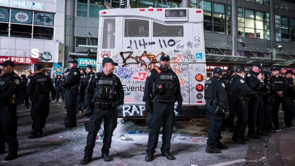 Police watch over a bus which was damaged after Toronto Raptors supporters celebrated in the streets after the Raptors defeated the Golden State Warriors during Game 6 NBA Finals to win the NBA Championship, in Toronto on Thursday, June 13, 2019. THE CANADIAN PRESS/Christopher Katsarov