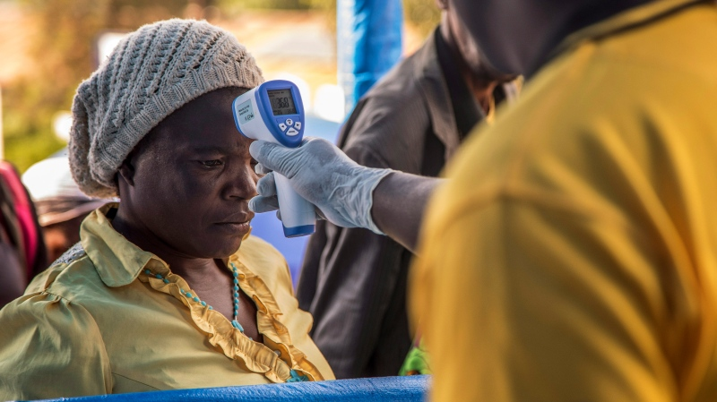 In this photo provided by the International Rescue Committee, a Congolese refugee is screened for Ebola symptoms at the IRC triage facility in the Kyaka II refugee settlement in Kyegegwa District in western Uganda, June 13, 2019. (Kellie Ryan/International Rescue Committee via AP)