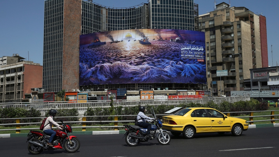 In this Wednesday, May 29, 2019 photo, People drive at Vali-e-Asr Square in downtown Tehran where an anti-Israeli billboard is place ahead of the Al-Quds, Jerusalem, Day, Iran. (AP Photo/Ebrahim Noroozi)