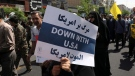 In this May 31, 2019 file photo, a demonstrator holds an anti-U.S. placard during the annual Quds, or Jerusalem Day rally in Tehran, Iran. The top line on the placard in Farsi translates to, Death to America, and the bottom line on the placard in Arabic translates to, Death to America. (AP / Vahid Salemi)
