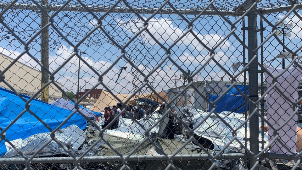 "In this June 1, 2019, photo, provided by New Mexico State University professor Neal Rosendorf, migrants are seen through fencing inside a temporary outdoor encampment where they're waiting to be processed in El Paso, Texas. Rosendorf said it resembled a ""human dog pound."" (Neal Rosendorf via AP)"