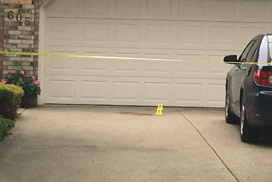 A pair of evidence markers are placed next to what appears to be a blood stain on the driveway of a Tecumseh home where a fatal shooting occurred on Friday, June 14, 2019.
