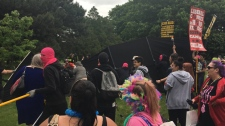 LGBTQ activists hold a black fabric barrier in front of religious demonstrators protesting their existence in Gage Park, Hamilton on June 15, 2019. (Twitter/@Soycrates)