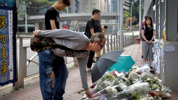 Mourners lay flowers on the site where a man fell to his death a day earlier after hanging a protest banner on the scaffolding of a shopping mall in Hong Kong, Sunday, June 16, 2019. (AP Photo/Vincent Yu)