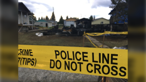 Police tape mark off the scene of a fatal house fire in Plamodon, Alta.