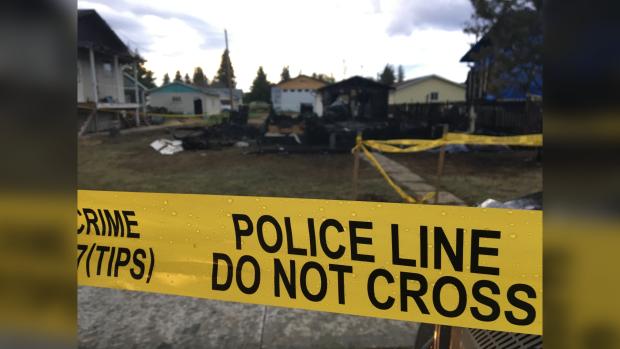 Police tape mark off the scene of a fatal house fire in Plamondon, Alta.