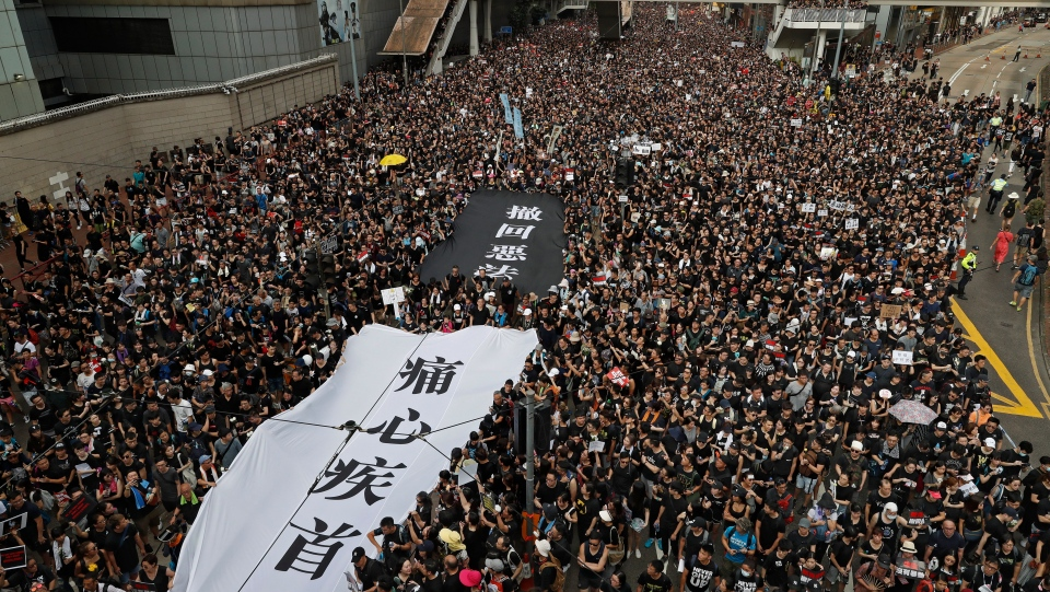 "Protesters carry a huge banner reading ""Our hearts are torn to pieces. Withdraw the monstrous bill"" as they march on the streets against an extradition bill in Hong Kong on Sunday, June 16, 2019.  (AP Photo/Vincent Yu)"