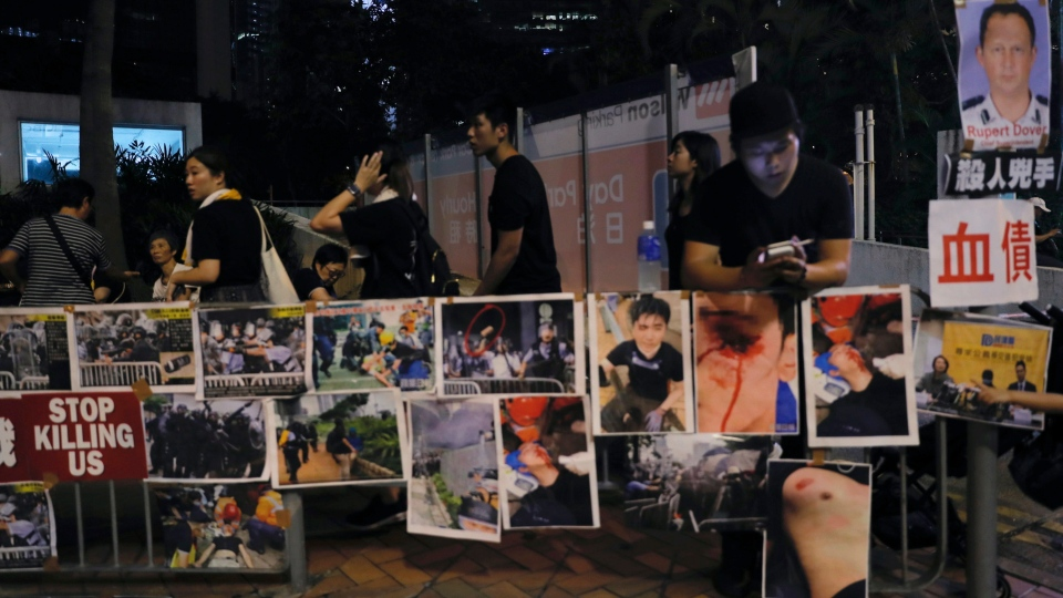 Protesters gather near photos of other protesters injured during Wednesday's violent protest, as well as photos of police commander they claimed had authorized the use of aggressive tactics, in Hong Kong on Sunday, June 16, 2019. (AP Photo/Kin Cheung)