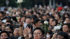 Protesters hold up flowers to pay respect for a man who fell to his death on Saturday after hanging a protest banner against an extradition bill in Hong Kong Sunday, June 16, 2019. HongKong residents were gathering Sunday for another massive protest over an unpopular extradition bill that has highlighted the territory's apprehension about relations with mainland China. (AP Photo/Kin Cheung)