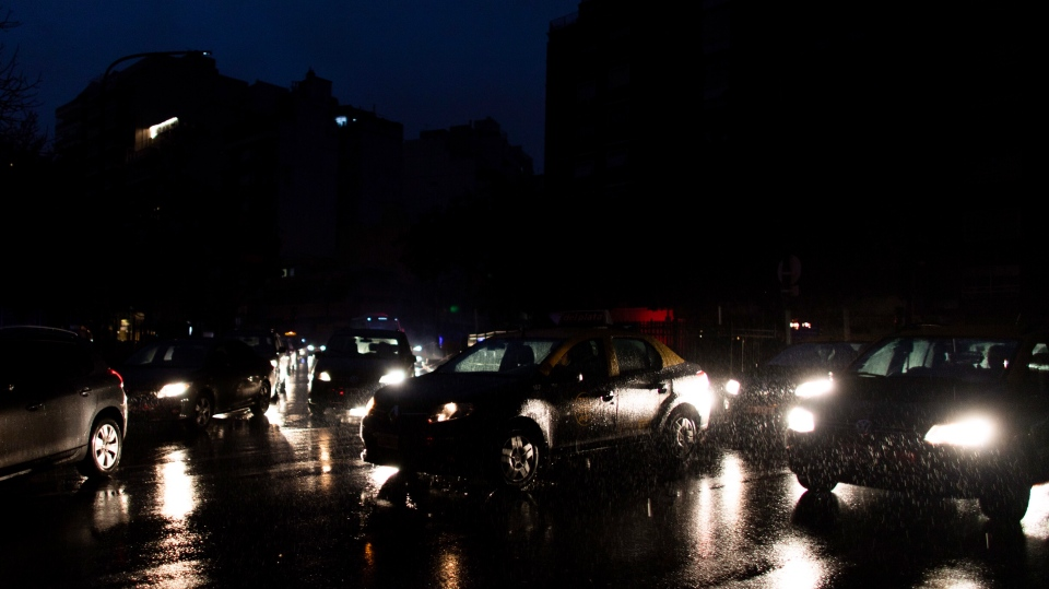 Cars drive through an unlit street during a blackout in Buenos Aires, Argentina, Sunday, June 16, 2019. (AP Photo/Tomas F. Cuesta)